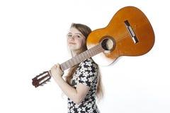 De glimlachende tiener in kleding houdt gitaar op schouder in studio stock fotografie
