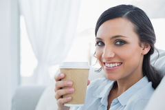 De glimlachende verleidelijke donkerbruine mok van de holdingskoffie Royalty-vrije Stock Foto