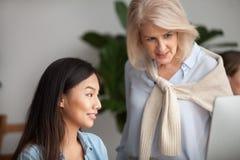 De glimlachende verouderde leider die het werk controleren of jonge Aziaat onderwijzen stelt tewerk stock afbeeldingen