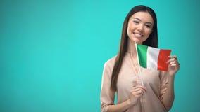 De glimlachende vlag van Italië van de dameholding, klaar om vreemde taal, Italiaanse school te leren stock videobeelden