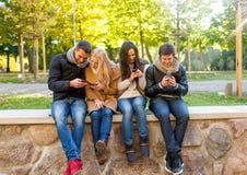 De glimlachende vrienden met smartphones in stad parkeren Royalty-vrije Stock Foto's