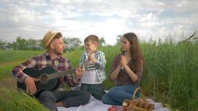 De glimlachende vrolijke vader speelt gitaar terwijl moeder met de dans en de klap van de kindjongen terwijl binnen het ontspanne stock video