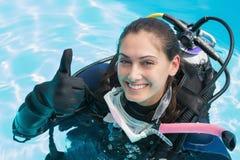 De glimlachende vrouw bij scuba-uitrusting de opleiding in zwembad het tonen beduimelt omhoog Stock Foto