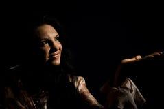 De glimlachende vrouw in dark maakt een presentatie Stock Afbeeldingen