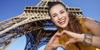 De glimlachende vrouw die gevormd hart tonen dient Parijs, Frankrijk in stock foto's