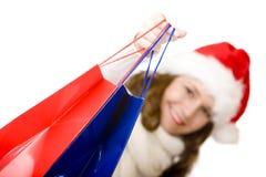 De glimlachende vrouw die van de Kerstman het winkelen van Kerstmis doet Stock Foto