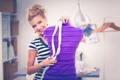 De glimlachende vrouw die van de manierontwerper zich dichtbij ledenpop in bureau bevinden Stock Foto
