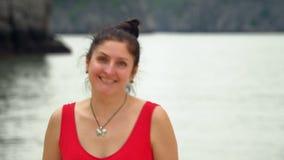 De glimlachende vrouw gaat langs de kust op het eiland De vrouw op het eiland in een baai Het gezichts dichte omhooggaand van de  stock footage