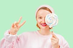 De glimlachende vrouw houdt suikergoedlolly op pastelkleur groene achtergrond stock foto