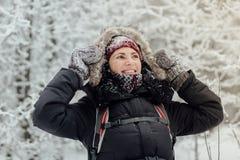 De glimlachende vrouw kleedde warme holding haar kap met sneeuwhandschoenen Royalty-vrije Stock Afbeeldingen
