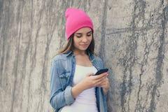 De glimlachende vrouw kleedde zich in vrijetijdskleding en roze hoed die op de straat muur en het gebruiken van Internet voor het royalty-vrije stock foto's