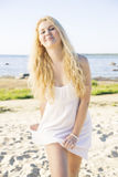 De glimlachende vrouw kronkelt zich in kleding bij strand Royalty-vrije Stock Afbeelding