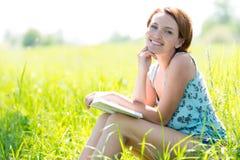 De glimlachende vrouw leest het boek bij aard Stock Foto