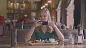 De glimlachende vrouw maakt een foto van lapje vlees in restaurant stock footage