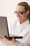 De glimlachende vrouw met laptop Stock Foto's
