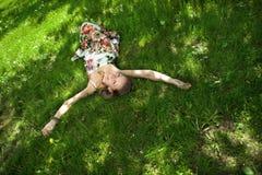 De glimlachende vrouw ontspant op het gras Royalty-vrije Stock Afbeeldingen