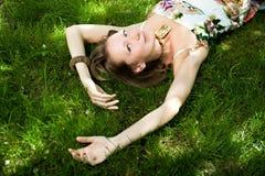 De glimlachende vrouw ontspant op het gras Stock Fotografie