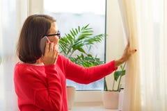 De glimlachende vrouw op middelbare leeftijd spreekt op de telefoon stock fotografie