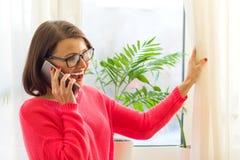 De glimlachende vrouw op middelbare leeftijd spreekt op de telefoon, opent de gordijnen en bekijkt uit het zonnige venster royalty-vrije stock afbeelding