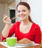 De glimlachende vrouw in rood eet boekweithavermoutpap Stock Fotografie