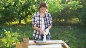 De glimlachende vrouw zet op beschermende glazen en handschoenen en begint hout te verwerken stock videobeelden