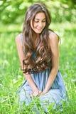 De glimlachende vrouw zit op groen gras Royalty-vrije Stock Afbeelding