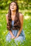 De glimlachende vrouw zit op groen gras Royalty-vrije Stock Foto