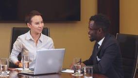 De glimlachende vrouwelijke Manager onderhandelt met haar Amerikaanse partner stock footage