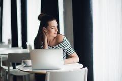 De glimlachende vrouwelijke schrijver werkt met haar nieuw idee bij lunch en kijkt door het venster voor het zoeken naar inspirat stock afbeeldingen