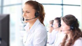 De glimlachende vrouwelijke vertegenwoordiger die van de klantendienst op hoofdtelefoon spreken Stock Fotografie