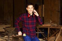 De glimlachende werkman kleedde zich in het geruite overhemd die de telefoon spreken bij de zaagmolen Hout op achtergrond stock foto's