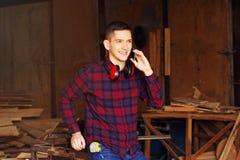 De glimlachende werkman kleedde zich in het geruite overhemd die de telefoon spreken bij de zaagmolen Hout op achtergrond stock afbeeldingen