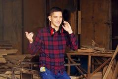 De glimlachende werkman kleedde zich in het geruite overhemd die de telefoon spreken bij de zaagmolen Hout op achtergrond royalty-vrije stock afbeeldingen