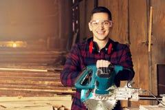 De glimlachende werkman kleedde zich in het geruite overhemd die met cirkelzaag bij de zaagmolen werken Hout op achtergrond royalty-vrije stock foto
