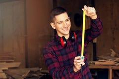 De glimlachende werkman kleedde zich in het geruite overhemd die met meetlint bij de zaagmolen werken Hout op achtergrond royalty-vrije stock foto