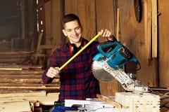De glimlachende werkman kleedde zich in het geruite overhemd die met meetlint dichtbij cirkelzaag bij de zaagmolen werken royalty-vrije stock afbeeldingen