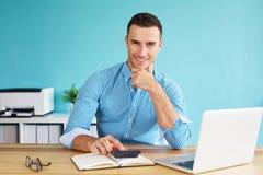 De glimlachende zakenman berekent belasting Stock Fotografie