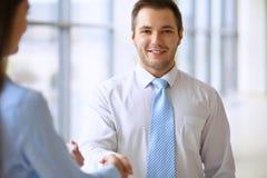 De glimlachende zakenman in bureau schudt handen met zijn partner Royalty-vrije Stock Fotografie