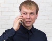 De glimlachende zakenman met verkoopt telefoon Stock Afbeelding
