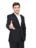 De glimlachende zakenman in zwart kostuum geeft handdruk Royalty-vrije Stock Fotografie