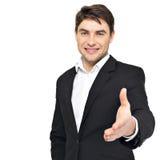 De glimlachende zakenman in zwart kostuum geeft handdruk Royalty-vrije Stock Foto