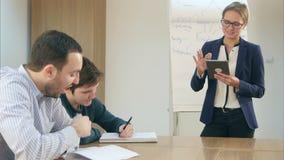 De glimlachende zekere vrouwelijke leraar met een tablet-PC hield in haar handen die zich voor klasse bevinden stock video