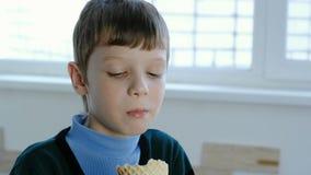 De glimlachende zeven-jaar-oude jongen likt roomijs die zich bij het venster bevinden stock videobeelden