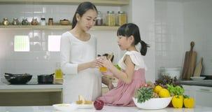De glimlachende zwangere moeder en de dochter genieten van zijnd samen in de keuken stock video