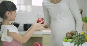 De glimlachende zwangere moeder en de dochter genieten van zijnd samen in de keuken stock videobeelden