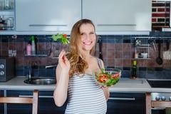 De glimlachende zwangere vrouw in keuken eet plantaardige salade Royalty-vrije Stock Afbeeldingen