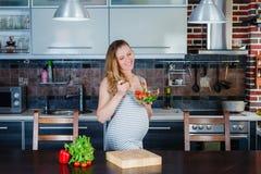 De glimlachende zwangere vrouw in keuken eet plantaardige salade Royalty-vrije Stock Foto