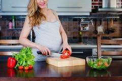 De Glimlachende zwangere vrouw in keuken kookt plantaardige salade Stock Foto's