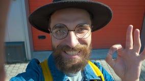 De glimlachmens van gebaard maakt een foto selfie gebruikend een mobiele telefoon op een stadsstraat stock video