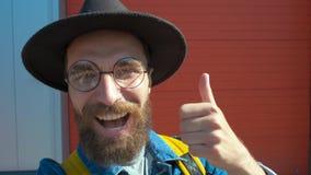 De glimlachmens van gebaard maakt een foto selfie gebruikend een mobiele telefoon op een stadsstraat stock footage
